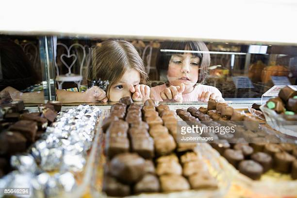 Girls pointing at candy in display case