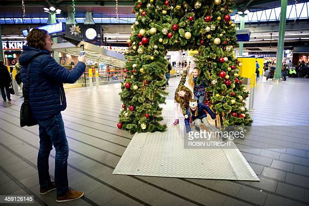 Girls pose for a picture under a Christmas tree at Amsterdam Airport Schiphol in Schiphol the Netherlands on December 23 2013 OUT