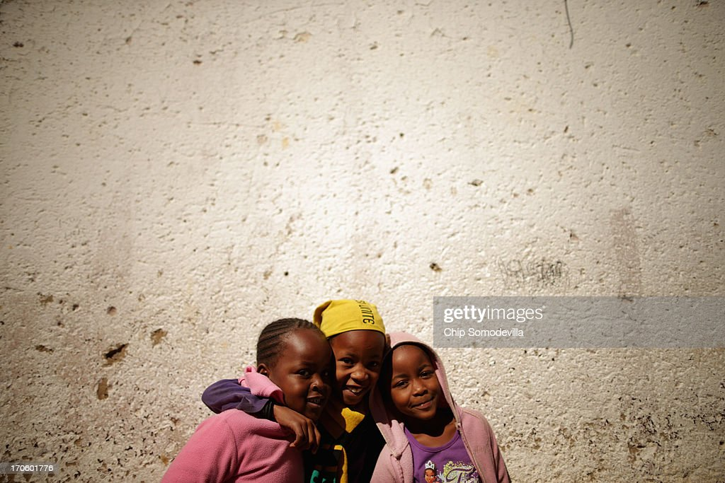 Girls pose for photographs in an alley behind shacks in the Alexandra Township around the corner from where former South African President Nelson Mandela lived in the 1940s June 15, 2013 in Johannesburg, South Africa. A leader of the anti-apartheid movement and the first democratically elected president of South Africa, Mandela is spending a seventh night in hospital and is reported to be responding better to treatment for a recurring lung infection.