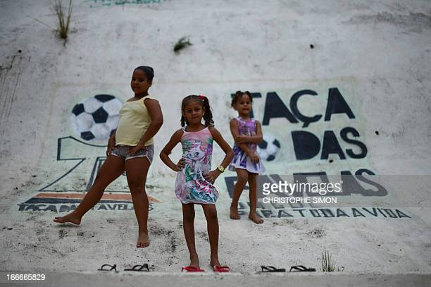 Girls pose next to a sign reading 'Shantytown's cup' on the wall of a football field in the Cidade de Deus shantytown Rio de Janeiro Brazil on April...