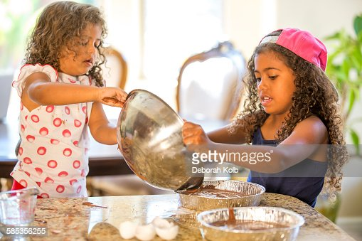 Girls pouring cake mix from mixing bowl into cake tins : Stock Photo