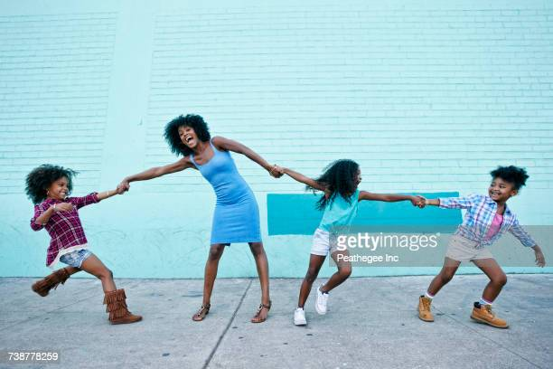 Girls pulling arms of woman in opposite directions