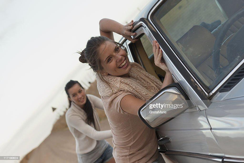 Girls pushing car : Stock Photo
