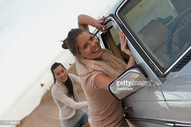 Girls pushing car