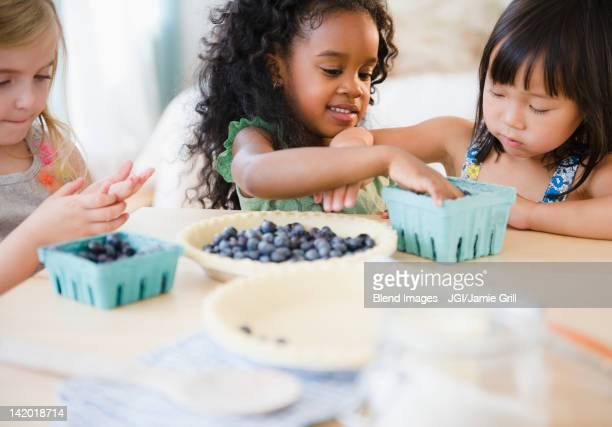 Girls putting blueberries into bowl together