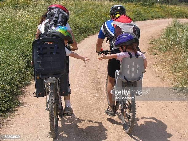 Girls reaching out on mountain bikes