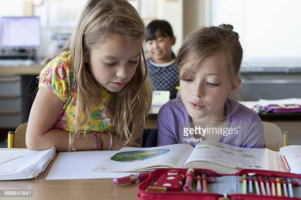 Girls reading book in classroom