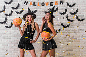 Beautiful girls in black dresses and witch hats are holding scary pumpkins and smiling, on background decorated for Halloween