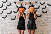 Beautiful girls in black dresses and witch hats are holding scary pumpkins, on background decorated for Halloween