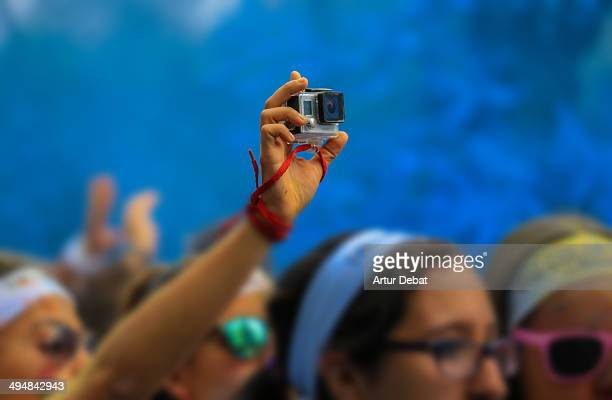 Girls recording in first person with GoPro in the Color Run by Desigual Blue color powder Barcelona Catalonia May 18th 2014 Wearable technology