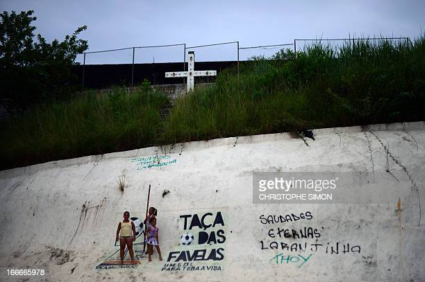 Girls remain near a sign reading 'Shantytown's cup' near a cross in a football field in the Cidade de Deus shantytown Rio de Janeiro Brazil on April...