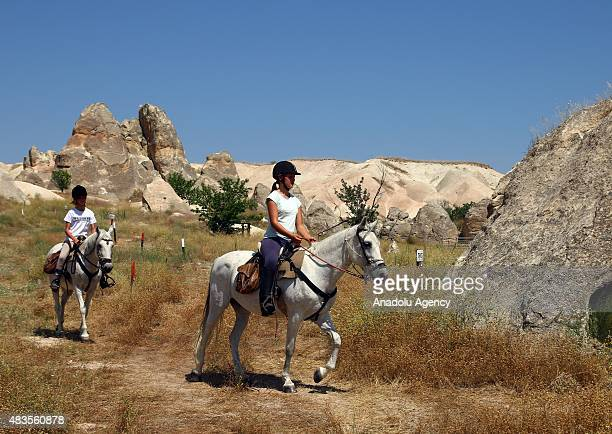 Girls ride horses near fairy chimneys in Cappadocia in Turkey's Nevsehir on August 4 2015 Opportunities to see volcanic valleys formed in millions of...