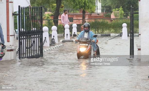 Girls ride scooty through waterlogged campus during heavy rains at Rajasthan University on August 23 2017 in Jaipur India