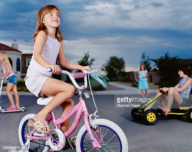 Girls (5-11) riding bicycles and scooters in street