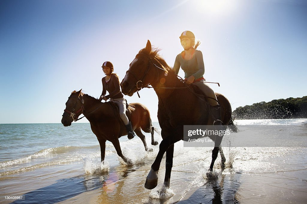 Girls riding horses on beach : Stock Photo