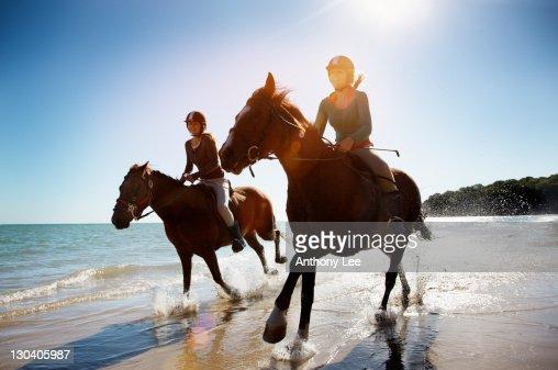 Girls riding horses on beach : Stock Photo
