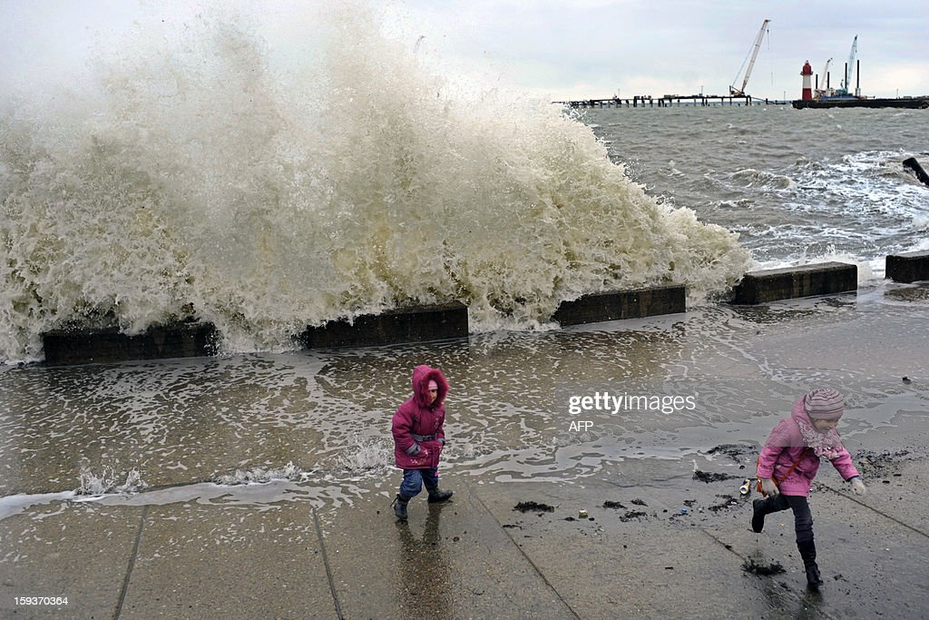 Girls run from a wave during a storm in the Russian Black Sea resort of Sochi on January 12, 2013.