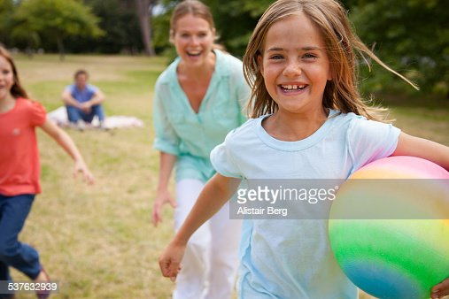 Girls running in park with their mother