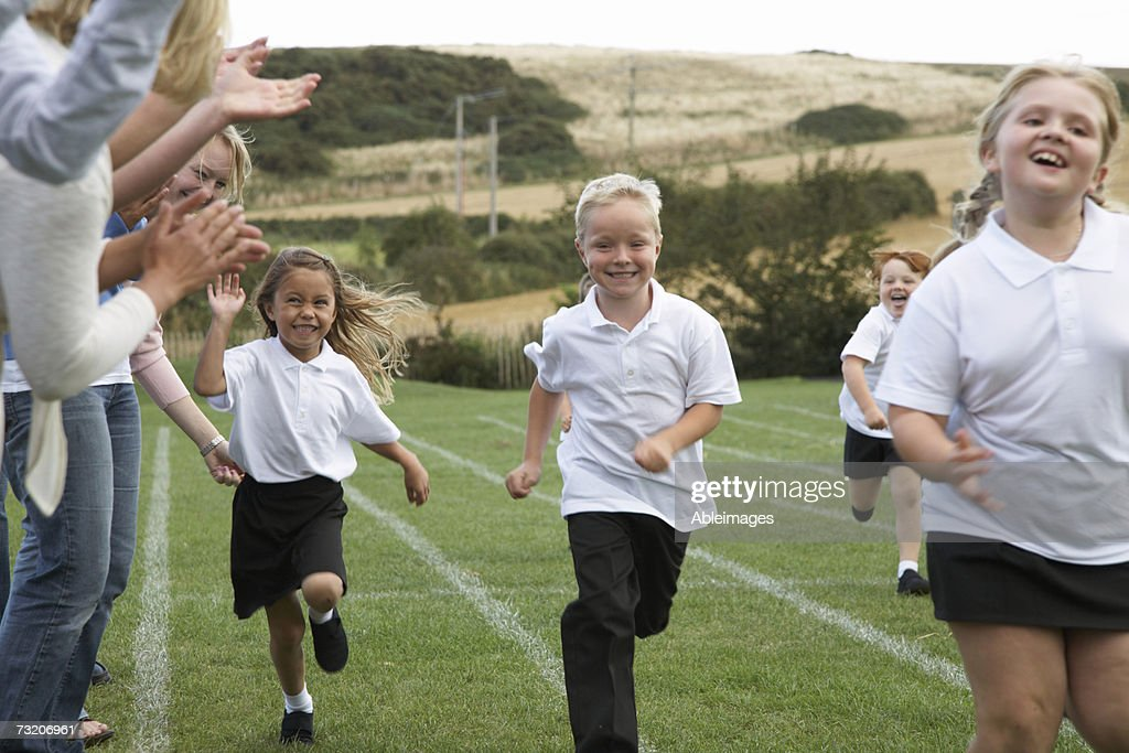 Girls (5-7) running on field with mothers cheering on sidelines : Stock Photo