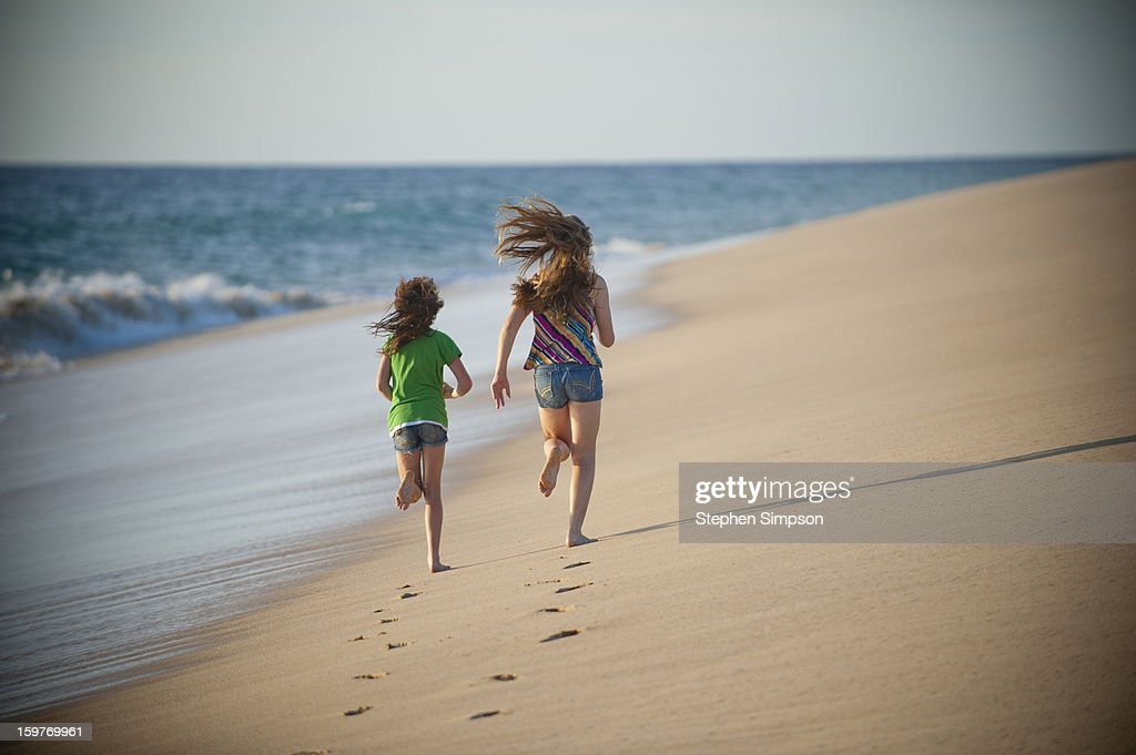 girls running on pristine empty beach : Stock Photo