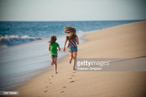 girls running on pristine empty beach : Stock Photo