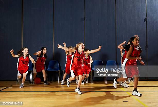 Girls (8-10) running onto basketball court, cheering
