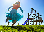 Girls (3-6) running to playground in field (low angle view)