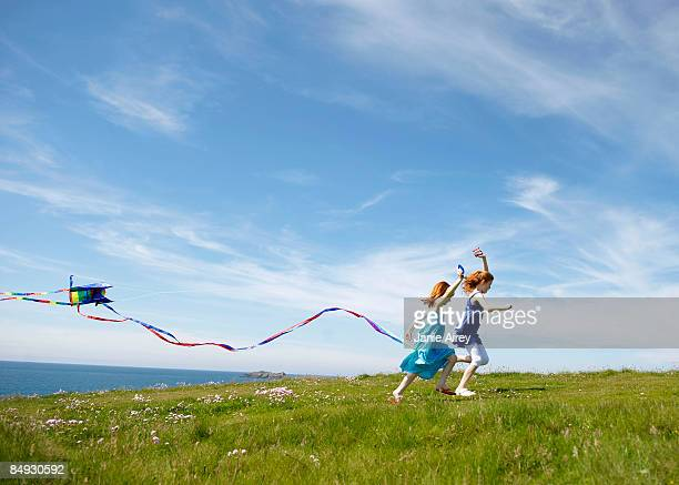 2 girls running with kites in field