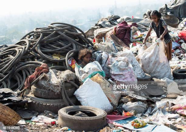Girls search through a rubbish tip by the Kapali Bagan slum for useful artifacts to sell on December 10 2013 in Kolkata India Almost one third of the...