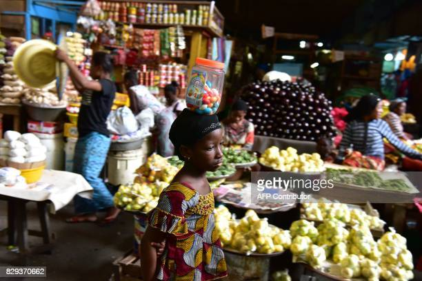 TOPSHOT A girls sells sweets at the large market of Adjame a popular district of Abidjan on August 10 2017 The Ivorian government in a council of...