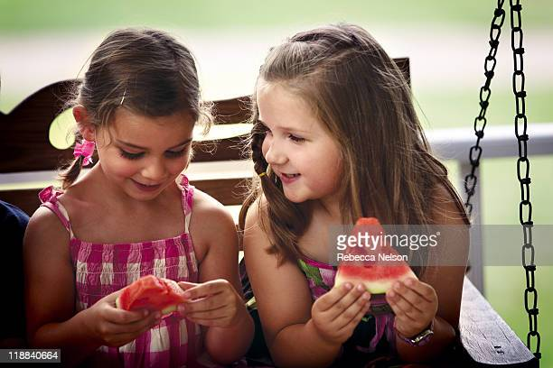Girls sharing smile and slices of watermelon