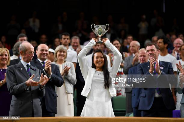 Girl's Singles final winner Claire Liu of the United States poses with her trophy as The Duke of Kent and AELTC Chairman Philip Brook applaud on...