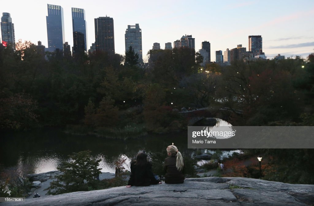 Girls sit on a rock in Central Park on the first day it opened following Superstorm Sandy on November 4, 2012 in New York City. With the death toll currently over 100 and millions of homes and businesses without power, the US east coast is attempting to recover from the effects of floods, fires and power outages brought on by Superstorm Sandy.