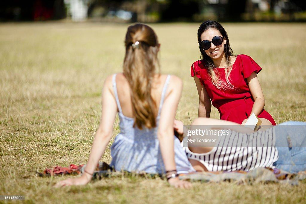 Girls sitting down on grass enjoying the sun : Stock Photo