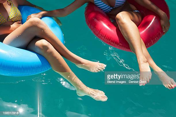 Girls sitting in inflatable rings in swimming pool