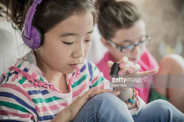 Girls sitting on bedroom floor painting fingernails