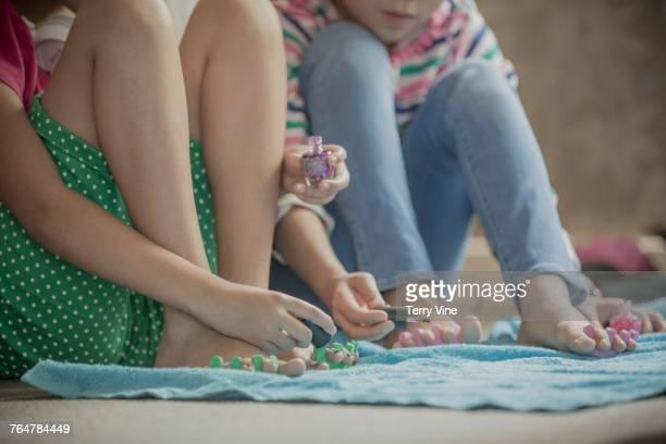 Girls sitting on bedroom floor painting toenails