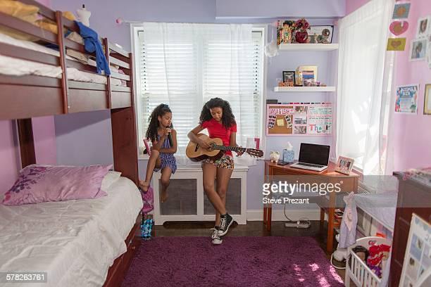 Girls sitting on bedroom windowsill singing and playing guitar