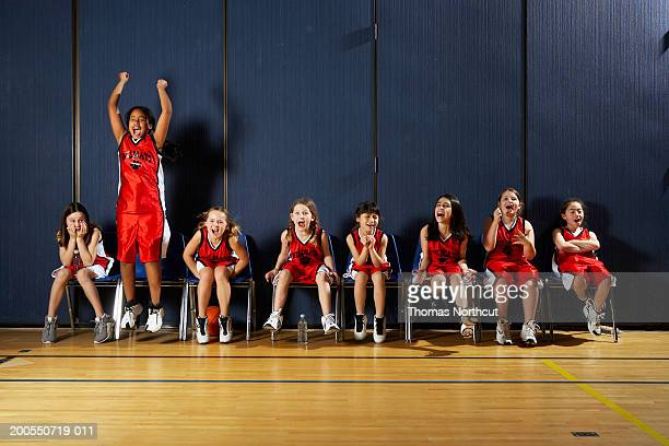 Girls (8-10) sitting on chairs beside basketball court, shouting