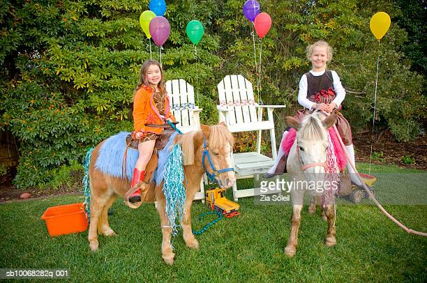 Girls (4-7) sitting on pony in back yard, smiling