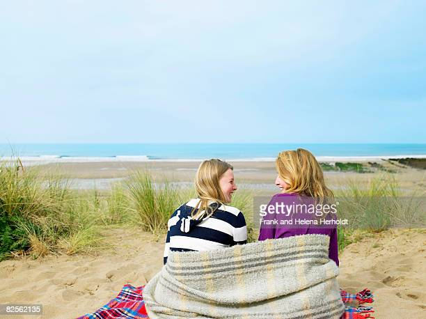 Girls sitting on sand dune with blanket