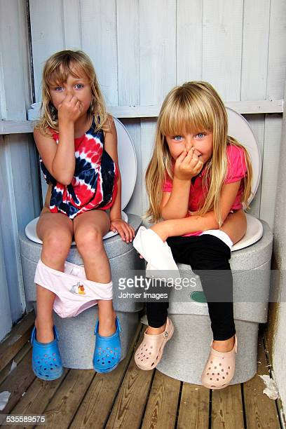 Girls sitting on toilets