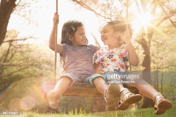 Girls sitting on tree swing together