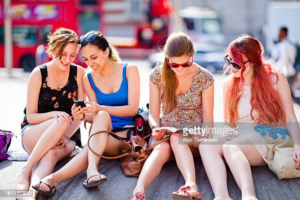 Girls sitting outdoors in a city