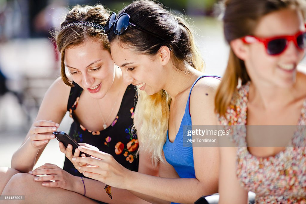 Girls sitting outdoors looking at a smartphone : Stock Photo