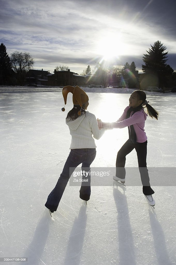 Girls (10-13) skating together on frozen lake, sunset, winter : Stock Photo