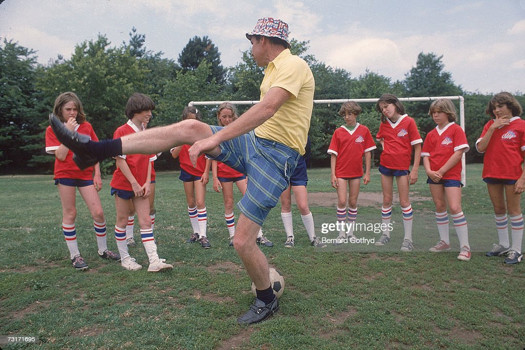 A girl's soccer team watches as their coach, dressed in a yellow shorts and checkered shorts, demonstrates kicking technique, Hicksville, Long Island, New York, 1978.