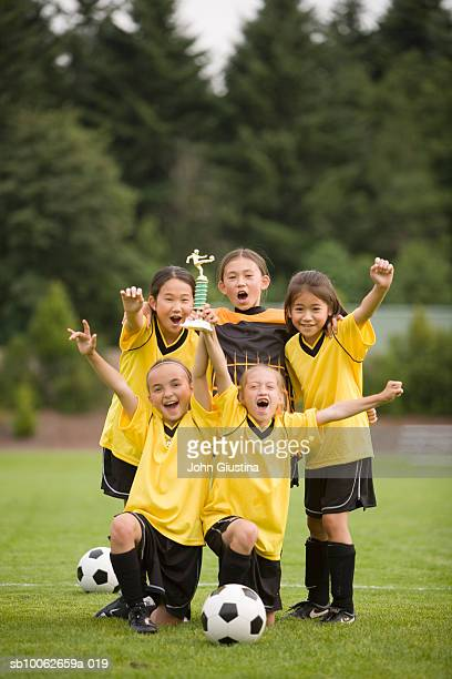 Girls (8-13) soccer team with trophy, laughing, portrait