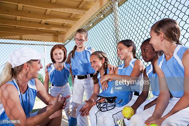 Girls softball team in dugout with coach