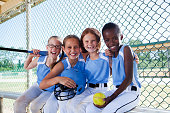 Multi-ethnic girls (7-9 years) on softball team at the ball park, sitting in dugout.